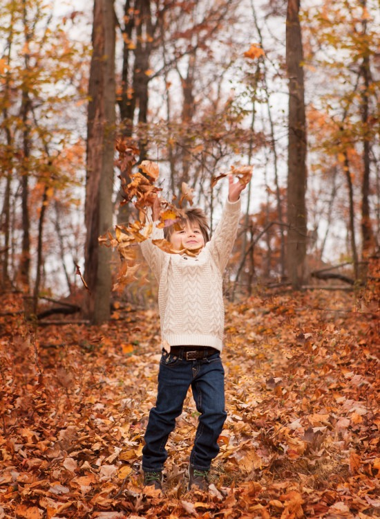 little boy throwing leaves